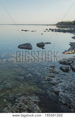 Dead calm morning image of shallow and clear lake huron water and limestone rocks along theshoreline. A small tree-covered peninsula is on the horizon. Overall feeling is a calm peaceful tranquil serene and wild background.