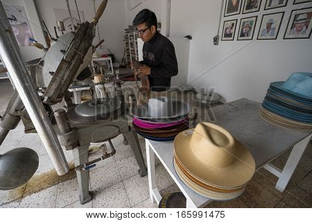 July 20, 2016 Cuenca, Ecuador: a man is using the hot steam rim press machine to give shape to Panama hats