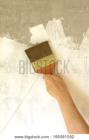 Woman's hand with brush painted wall repair vertical photo
