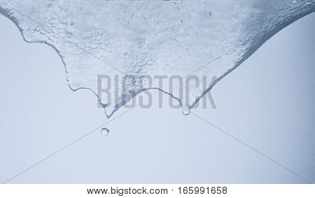 Transparent icicles melting and dripping water abstract