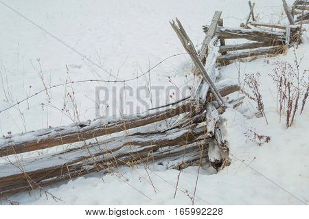 Wintery snow background of a split rail cedar fence with a sprinkle of snow