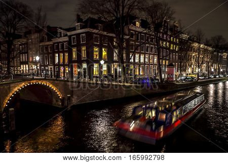 AMSTERDAM NETHERLANDS - JANUARY 11 2017: Beautiful night city canals of Amsterdam with moving passanger boat. January 11 2017 in Amsterdam - Netherland.