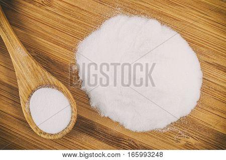Baking soda in a wooden spoon on a wooden board poster