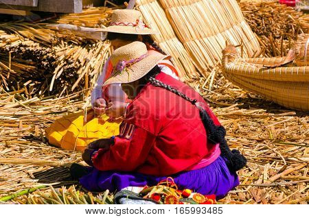 UROS FLOATING ISLANDS PERU - SEPTEMBER 19: Women make handicrafts on one of the Uros Floating Islands in Peru on Lake Titicaca on September 19 2014