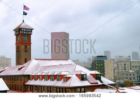 Train station and snow in Portland Oregon with the Oregon and American flag flying above it