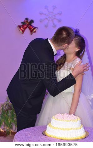 The groom kisses the bride on the background of cake.