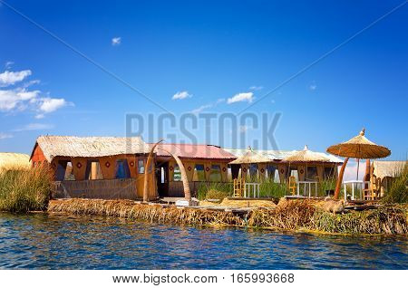One of the Uros manmade floating islands on Lake Titicaca in Peru with a dog on it
