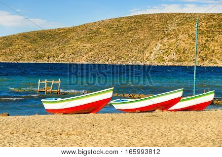 Three matching boats on the shore of Lake Titicaca on the Island of the Sun in Bolivia