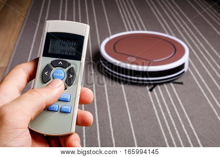 Hand hold remote control for robotic vacuum cleaner on grey carpet smart cleaning technology