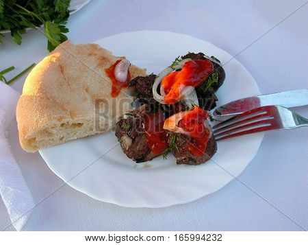 a barbecue with ketchup an onion pita