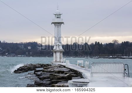 The Paquis pier and lighthouse covered with ice after a winter storm on Lake Geneva Switzerland.