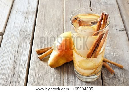 Pear, Ginger, Cinnamon Detox Water In A Glass Against A Rustic Wood Background