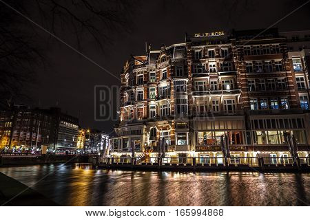 AMSTERDAM NETHERLANDS - JANUARY 08 2017: City sights of Amsterdam centre at night. General views of city landscape and architecture. January 08 2017 in Amsterdam - Netherlands.