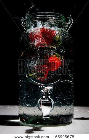Strawberries dropped into water dispenser full of water