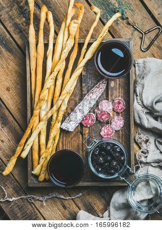 Wine and appetizers set. Italian Grissini bread sticks, dry cured pork meat sausage, black olives in jar and red wine in glasses in wooden tray over rustic wooden background, top view