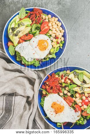 Healthy breakfast bowls with fried egg, chickpea sprouts, seeds, fresh vegetables and greens over grey concrete background, top view. Clean eating, dieting, healthy lifestyle, vegetarian food concept