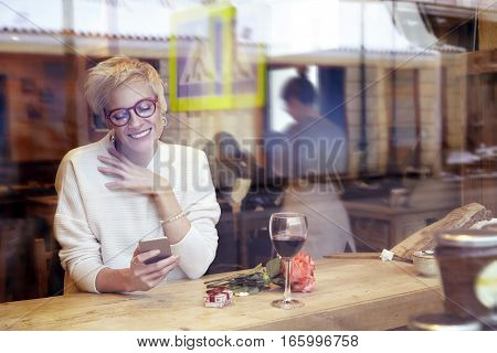 Beautiful blonde woman wearing eyeglasses messaging by mobile phonein cafe. Got a love message. Present box and rose flowers on wooden table. Romantique breakfast for a date or St. Valentine's Day.