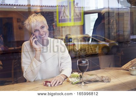 Beautiful blonde woman talking by mobile phone in cafe. Romantique breakfast for a date or St. Valentine's Day. Present box and rose flowers.