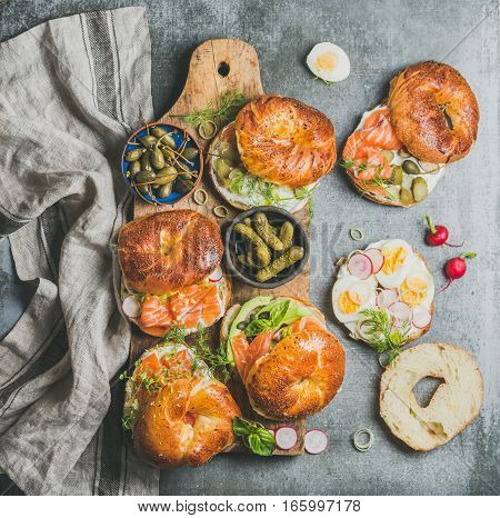 Variety of bagels with smoked salmon, eggs, radish, avocado, cucumber, greens and cream cheese for breakfast, healthy lunch, party or takeaway on wooden board over grey concrete background, top view