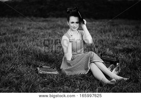 Portrait Of Young Pinup Girl Wearing At Retro Vintage Old-fashioned Dress In Peas Sitting On Grass W
