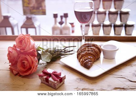 Romantic breakfast for Valentine's Day celebrate. Present box rose flowers fresh croissant wine on wooden table. Focus on croissant.
