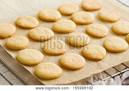 Orange butter cookies on a baking paper and wire rack. White wooden table. Top view