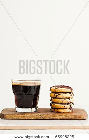 Morning black coffee and stack of butter cookies with chocolate drizzle on wooden board. White background. Copyspace for text.