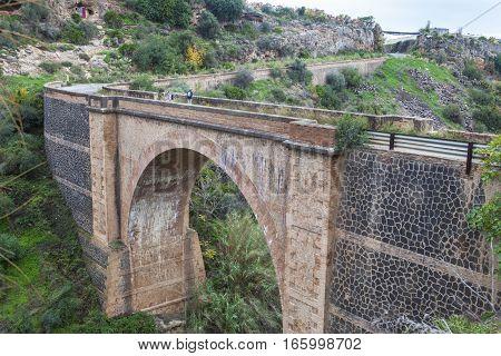 Nerja Spain - december 5 2016: Couple hiking by Old national highway bridge Nerja Malaga Spain