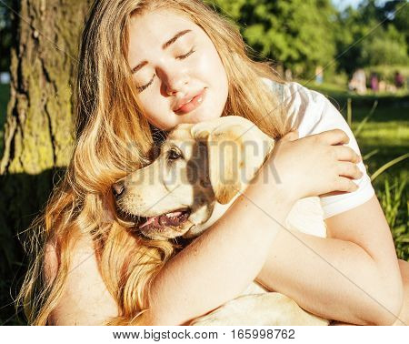 young attractive blond woman playing with her dog in green park at summer, lifestyle people concept, true friendship