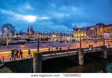 AMSTERDAM NETHERLANDS - JANUARY 12 2017: Old Dutch bridge at night time against rush clouds on January 12 2017 in Amsterdam - Netherlands.