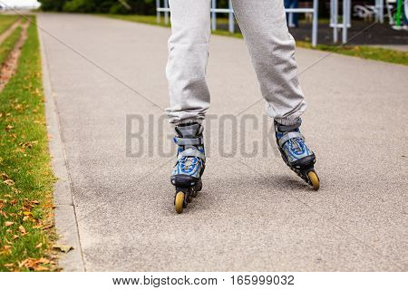 City sports and outdoor activities. Healthy lifestyle exercising and wellbeing. Free time hobby and having fun. Close up on legs in sportswear riding rollerblades.