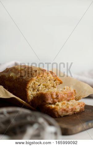 Cut of glazed applesauce oatmeal loaf cake on a wooden board. Copyspace