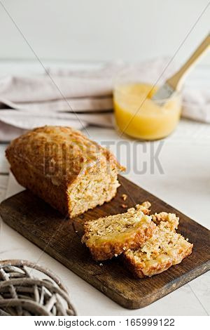 Slices of a glazed applesauce oatmeal bread on a white marble table. Ideal healthy breakfast with coffee and loaf cake.