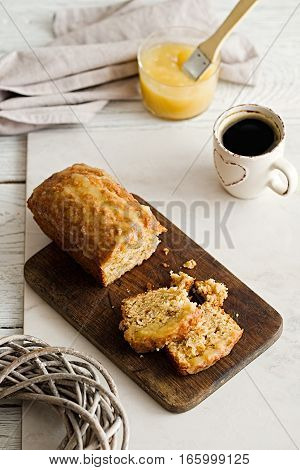 Glazed applesauce oatmeal sliced loaf cake on a white marble background. Ideal healthy breakfast with coffee