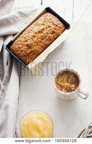 Glazed applesauce oatmeal bread in baking pan on a white marble table. Ideal healthy breakfast with a hot coffee and loaf cake.