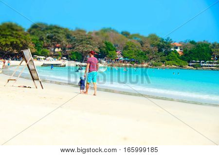Dad and a kid walking on the beach. Crystal turquoise sea water on Koh Samet island in Thailand. Perfect getaway in warm tropical country
