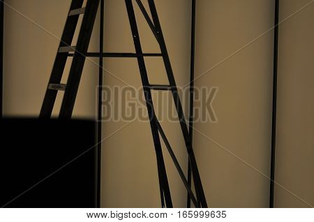 Close up silhouette of a ladder and a dimly lit wall