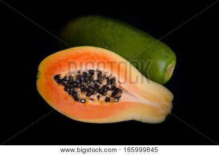 Papaya fruit whole and sectioned isolated on black background.