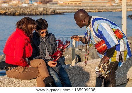 FIUMICINO LAZIO ITALY - FEBRUARY 13 2011: African peddler begging couple to buy some african art objects in the small port of Fiumicino. Many poor immigrants dealing with this for a living.