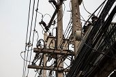 Few utility poles complicated wires and a lot of telephone cables against the gray sky. Many chaotic electric and phone cables in a Thai city poster