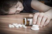Young woman commiting suicide by overdose of pills. poster