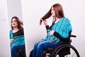 Disability beauty invalid happiness concept. Disabled girl looking at mirror. Crippled lady sitting at wheelchair doing combing her hair. poster