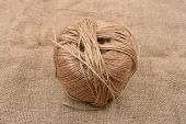 Close up of hank of twine reel of rope ball of hemp thread on jute background poster