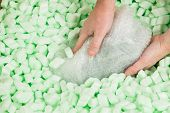 Hands placing a bubble wrapped parcel in polystyrene loosefill. poster