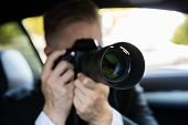 Private Detective Sitting Inside Car Doing Surveillance Work Photographing With Camera poster