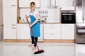 Young Cleaner Housemaid Sweeping Floor With Broom In Kitchen poster