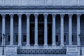 Neoclassical building front with corinthian columns colonnade, resembling a Greek or Roman temple. By architectural style it looks like a government or other public facility as a college / university, administration building or law court. poster