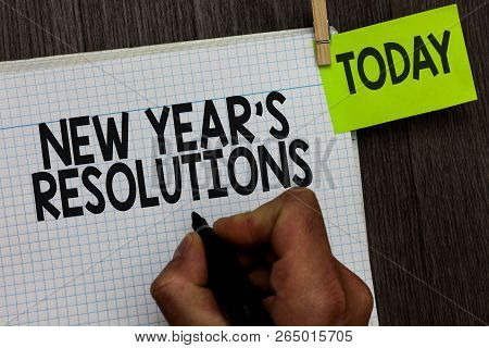 Word writing text New Year s is Resolutions. Business concept for Wishlist List of things to accomplish or improve Man holding marker notebook clothespin hold reminder wooden background. poster