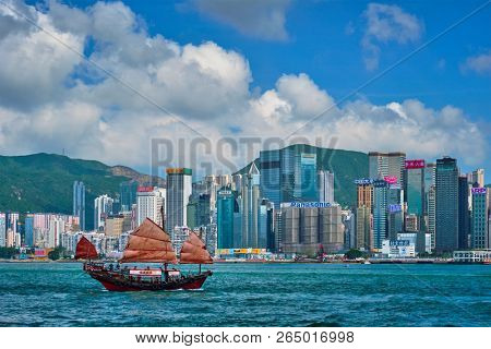 HONG KONG, CHINA - MAY 1, 2018: Hong Kong skyline cityscape downtown skyscrapers over Victoria Harbour in the evening with junk tourist ferry boat on sunset. Hong Kong, China