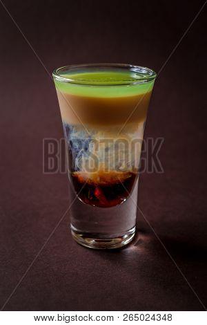 Hiroshima alcoholic shot glass with absent, sambuca, irish cream on elegant dark brown background. poster